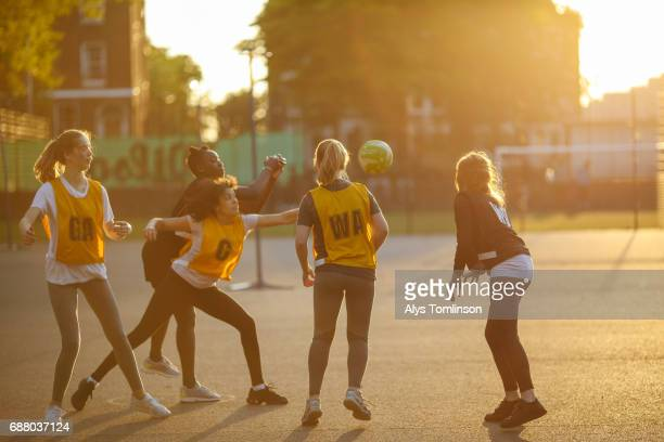group of netball players playing on city outdoor court at sunset