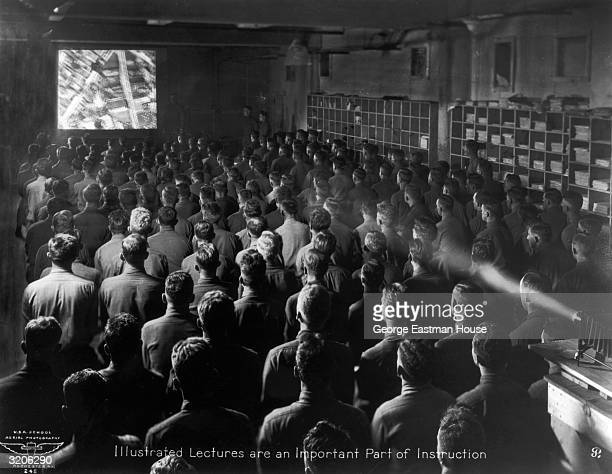 A group of new recruits watch an instructional film depicting an aerial view of a city in a darkened room during Army training World War I