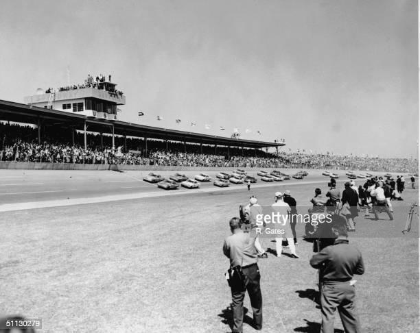 A group of news cameramen and photographers film a pack of cars racing during the Daytona 500 race at Daytona Speedway Daytona Beach Florida 1960s
