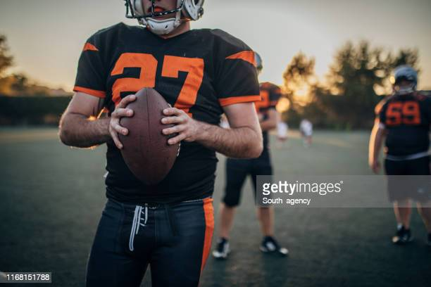 group of nfl players on field - ncaa stock pictures, royalty-free photos & images