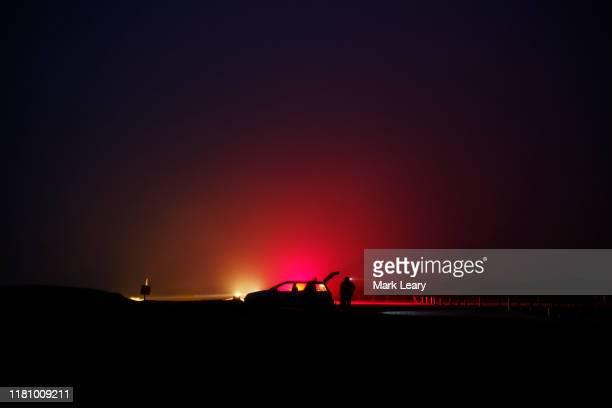 a group of night fishermen return to their cars after night fishing at a beach - グイチアン ストックフォトと画像