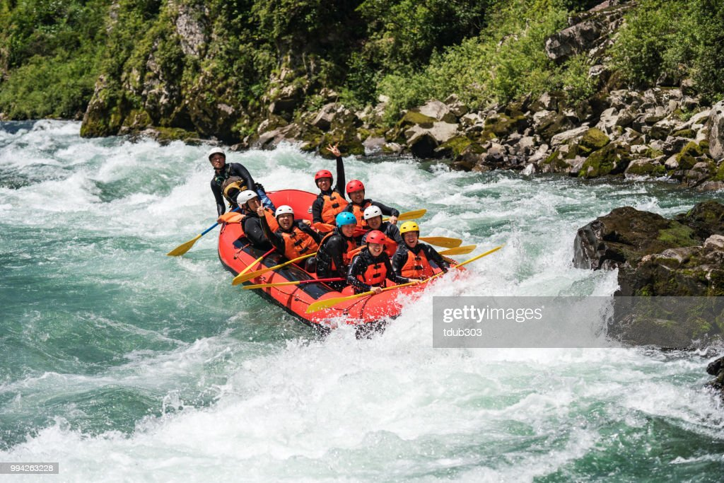 Group of nine men white water river rafting together : Stock Photo