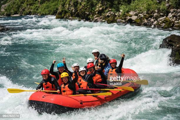 group of nine men white water river rafting together - rafting stock pictures, royalty-free photos & images