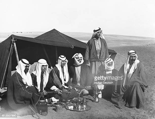 A group of nomadic Bedouins drink coffee outside a tent in the Transjordanian desert