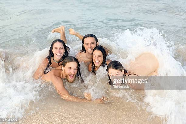 a group of nude young people smile at the viewer while skinny dipping in the ocean - skinny dipping stockfoto's en -beelden