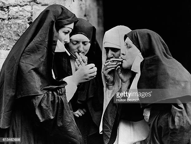 A group of nuns enjoy cigarettes