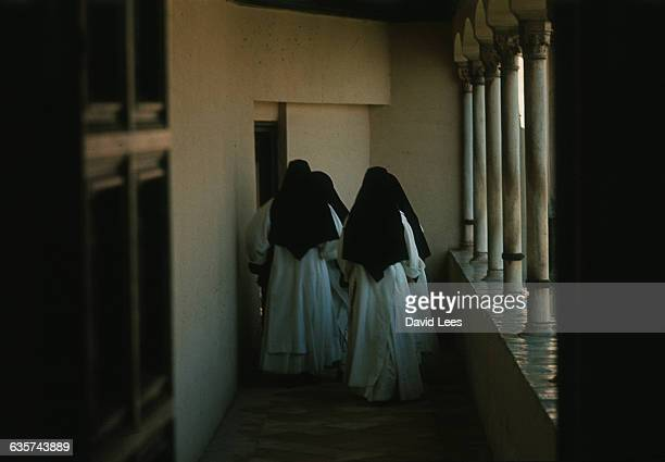 A group of nuns walk down a convent corridor in Granada Spain | Location Granada Spain