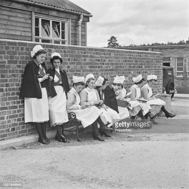 Group of nurses take the opportunity to read, write letters, knit and chat whilst off duty at St Thomas' Hospital's wartime site in Godalming, Surrey...
