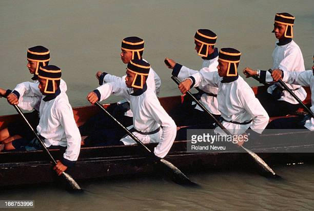 Group of oarsmen in traditional costumes on a boat during a boat racing festival in Bangkok..
