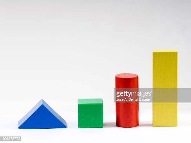 Group of objects of different geometric forms of wood, triangle, bucket, cylinder and rectangle on a white background.