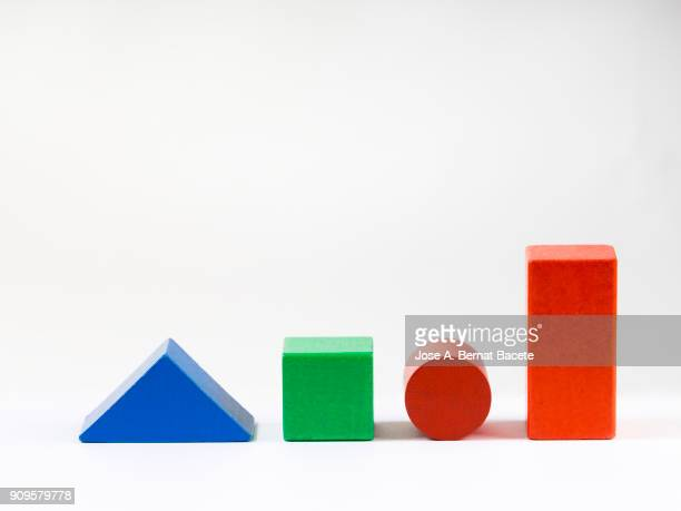 Group of objects of different geometric forms of wood, triangle, cube, circle and rectangle on a white background.