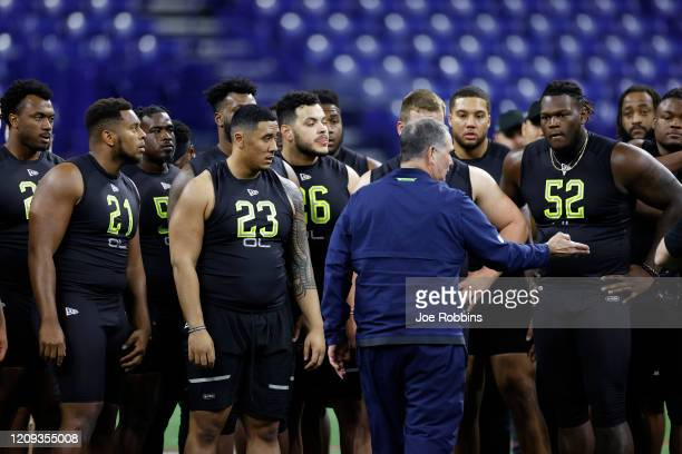 A group of offensive lineman listen to a coach as they prepare for a drill during the NFL Combine at Lucas Oil Stadium on February 28 2020 in...