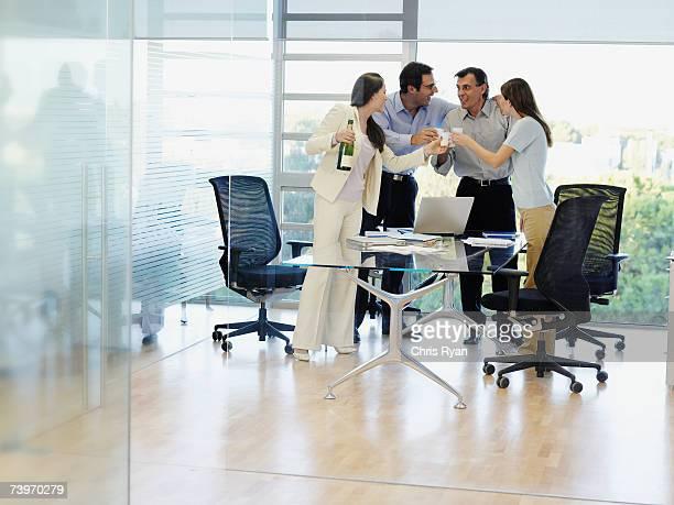 Groupe d'employés de bureau accompagné de champagne et de boire