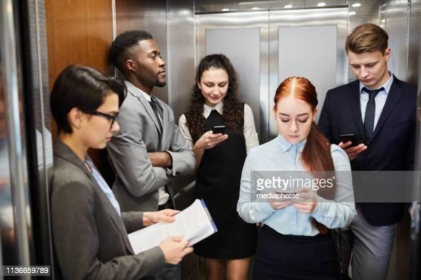 grupo de trabalhadores de escritório com os telefones no elevador - elevador - fotografias e filmes do acervo
