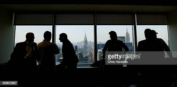 A group of officials and journalists stand by the windows on the 59th floor of the Citycorp building before a press conference announcing the arrival...
