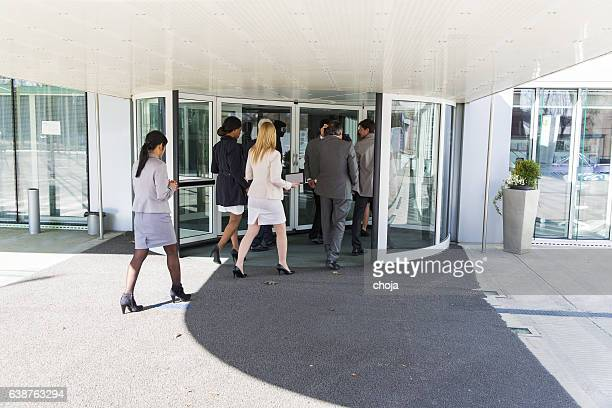 Group of ofiice worker entering in  revolving door
