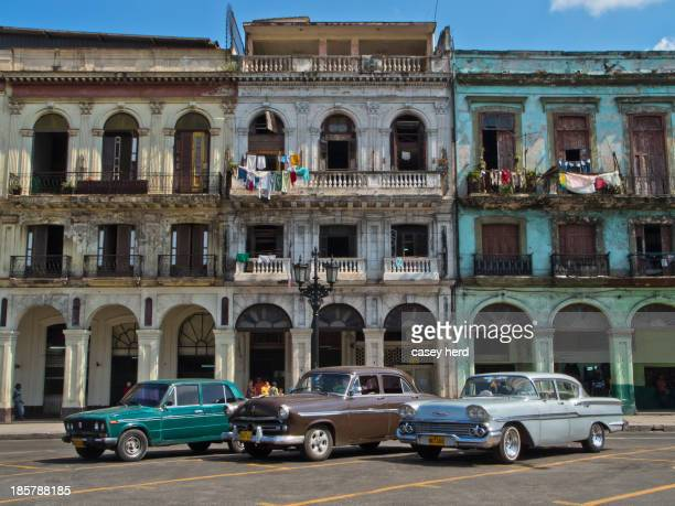 CONTENT] A group of old cars parked on the street in front of a cluster of colonial buildings in Havana Cuba