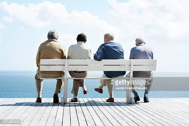 Group of old male friends sitting together on bench