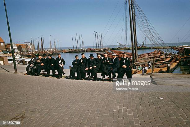 A group of old men dressed in black in the harbour of Volendam in the Netherlands circa 1965