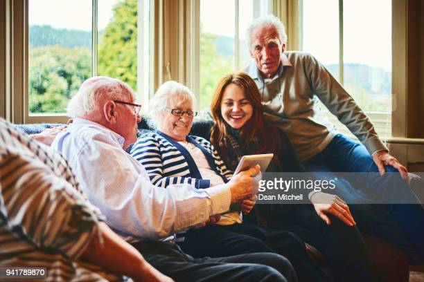 Group of old people with young woman using digital tablet