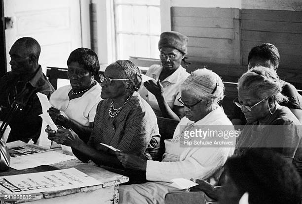 A group of older African Americans read sample ballots during a class in an Alabama church Civil rights groups held classes in Alabama and...