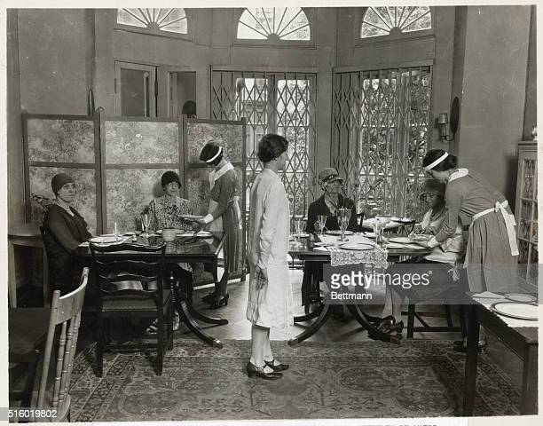 Group of older women taking luncheon in parlor attended by maids and hostess Photograph 1920's