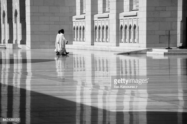 A group of Omanis walk at the exterior sahn (courtyard) of the Sultan Qaboos Grand Mosque in Muscat, Oman