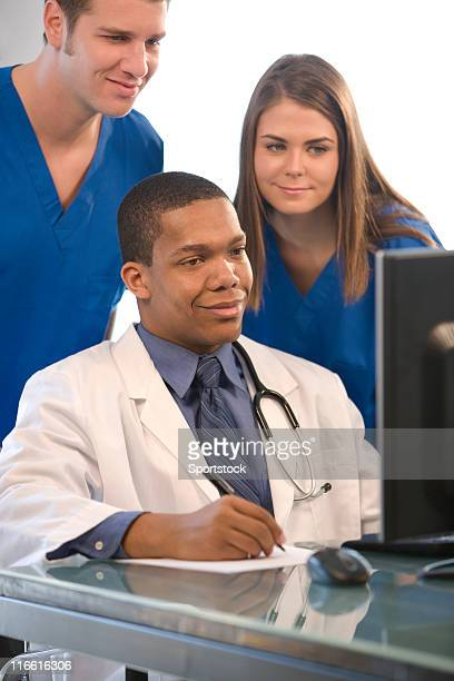 Group Of One Doctor And Two Nurses At A Desk