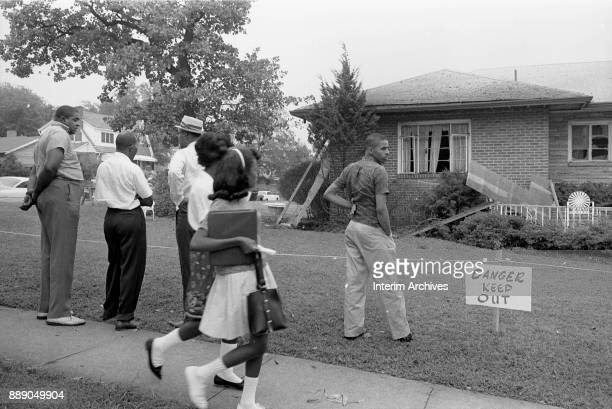 A group of onlookers stand on a sidewalk in front of NAACP attorney Arthur Shores' bombdamaged home Birmingham Alabama September 5 1963 A sign on the...