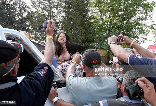 A group of onlookers take photographs as a woman displays her breasts in the back of a vehicle during Street Machine Summernats 21 Car Festival at...