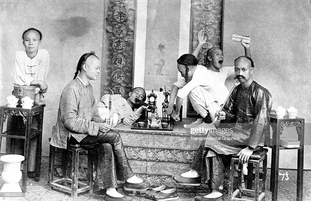 A group of opium smokers joke and pose in their 'den,' Shanghai