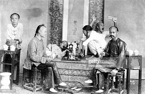 Group of opium smokers joke and pose in their 'den,' Shanghai, China, 1898.