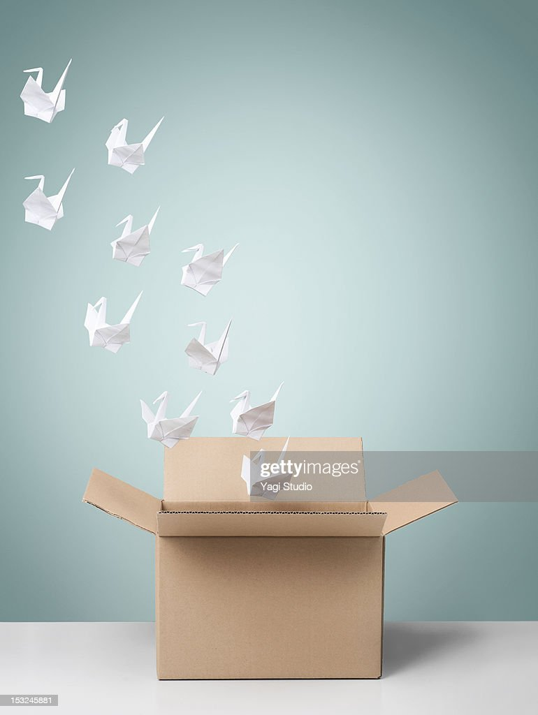 Group of origami cranes flying away from cardboard : Stock Photo