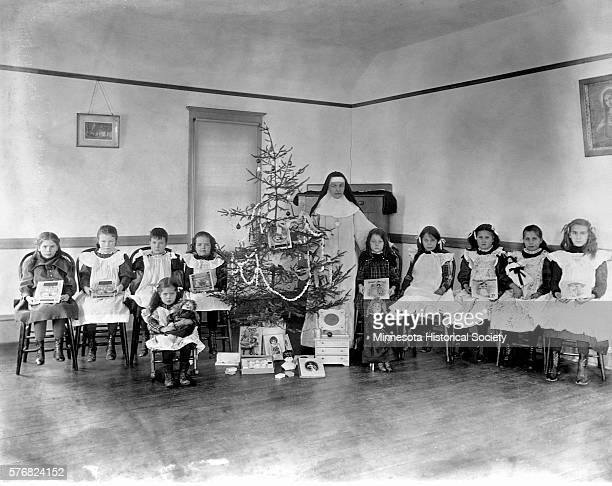 A group of orphans pose for a portrait with their new toys and a nun on Christmas