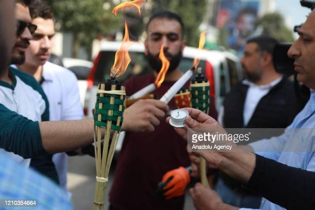 Group of Orthodox Christians light candles of citizens who stayed at their houses, with the Holy Fire brought from the Church of the Holy Sepulchre...