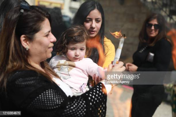 A group of Orthodox Christians light candles of citizens who stayed at their houses with the Holy Fire brought from the Church of the Holy Sepulchre...