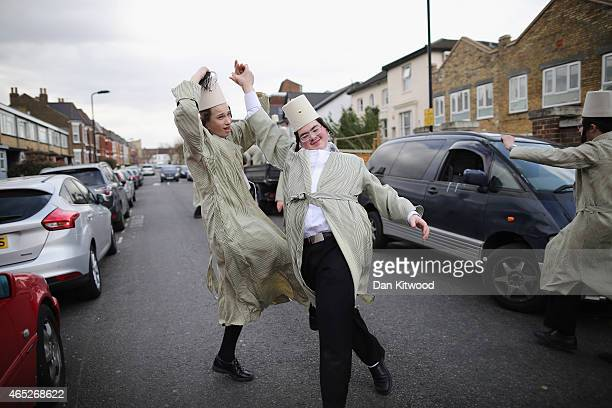 A group of Orthodox Jewish boys dance in the street before going into the home of a local businessmen while collecting money for their school during...