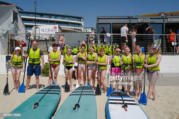 Group of paddle boarders formed from different households join together on Gyllyngvase Beach to pose for the photographer on July 19, 2021 in...