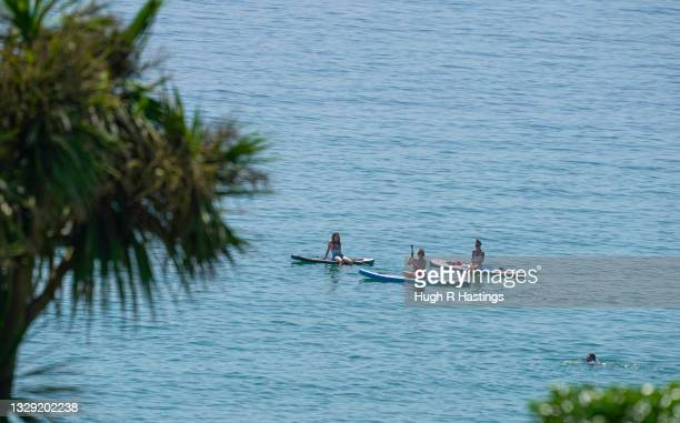 Group of paddle boarders were among holiday makers who gathered to enjoy the sun on Gyllyngvase Beach on July 17, 2021 in Falmouth, United Kingdom. A...