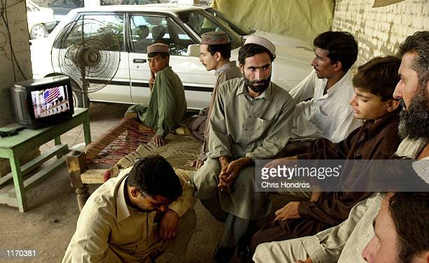 A group of Pakistani men and boys watch BBC television news about the US and British attacks on Afghanistan October 9 2001 in Peshawar Pakistan