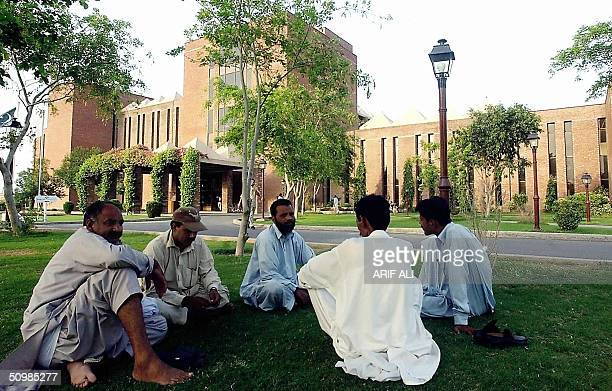 A group of Pakistani men talk as they sit infront of the Shaukat Khanum Memorial Cancer Hospital and Reseach Centre founded by former Pakistani...