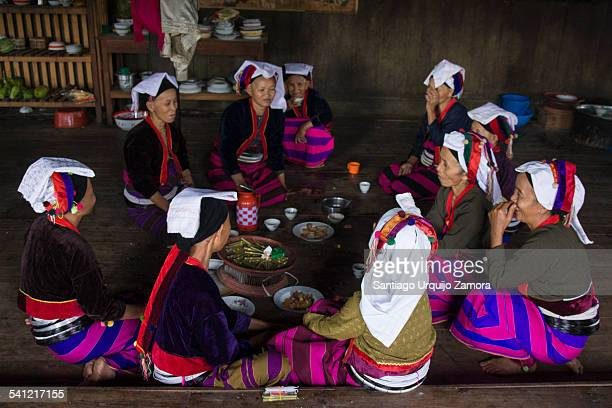 Group of Palaung women in traditional dresses eating on the floor around a table on a Buddhist monastery during a religious celebration, Hoo Kwat,...