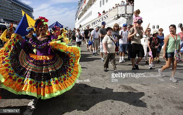 A group of 'Palenqueras' welcome tourists descending from cruises docked in the port of the Caribbean city of Cartagena Colombia on January 3 2011 A...