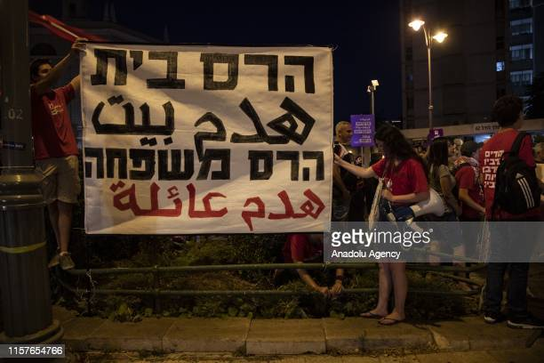 A group of Palestinian and Israeli activists hold placards as they gather to protest against Israels demolition policy aimed at razing Palestinian...