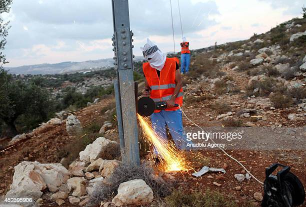 A group of Palestinian covering their faces damage the electricity pylons in Dolev city communal Israeli settlement in the West Bank as Israeli...