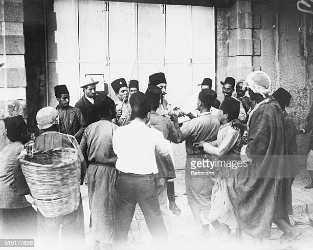 A group of Palestinians listen to a proclamation issued by the British high commissioners declaring that all disturbances of the peace either by...