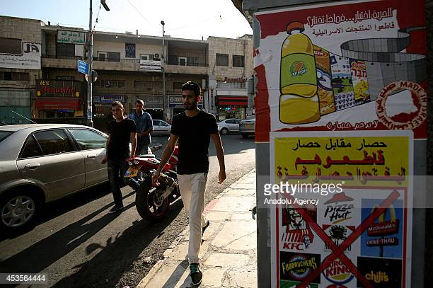 A group of Palestinians start a boycott campaign by hanging banners of Israeli products on public areas in Jerusalem on August 13 2014