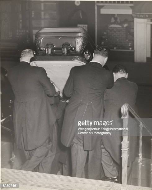 Group of pallbearers carry a coffin down the steps of a church after a funeral, while across the street, a restaurant awning reads '...Heaven,' New...
