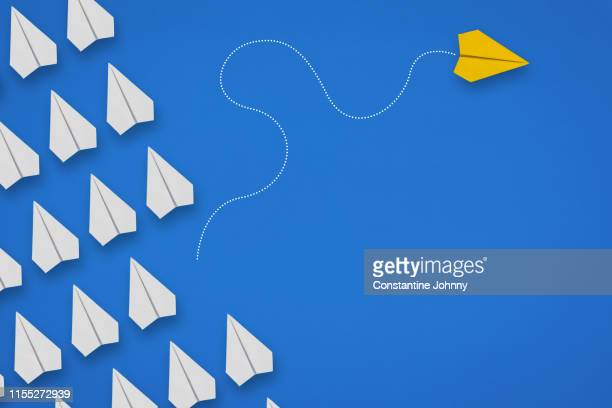 group of paper airplanes in same direction and one airplane moving to different direction. think different concept. - individualiteit stockfoto's en -beelden