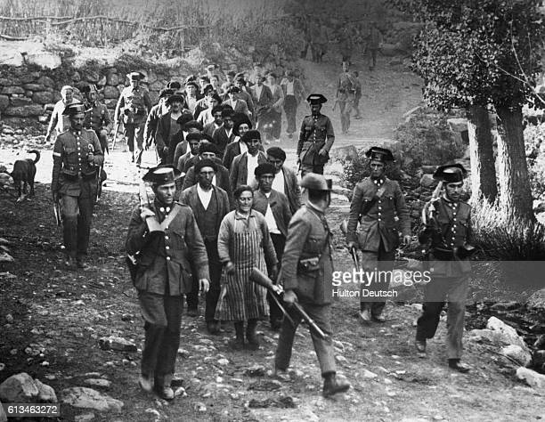 A group of participants in the revolt in Asturias during the Spanish Civil War are marched along under the arrest of civil guards